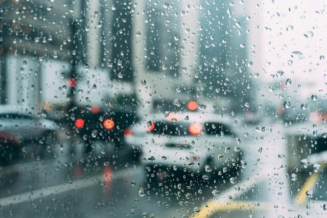 raindrop closeup on car window in downtown street