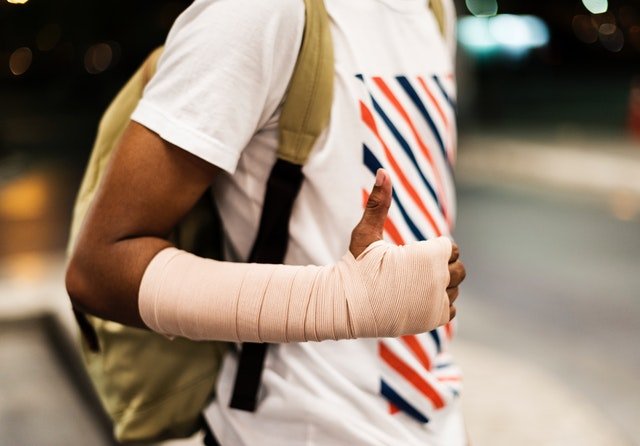 Young person with arm cast giving thumbs up